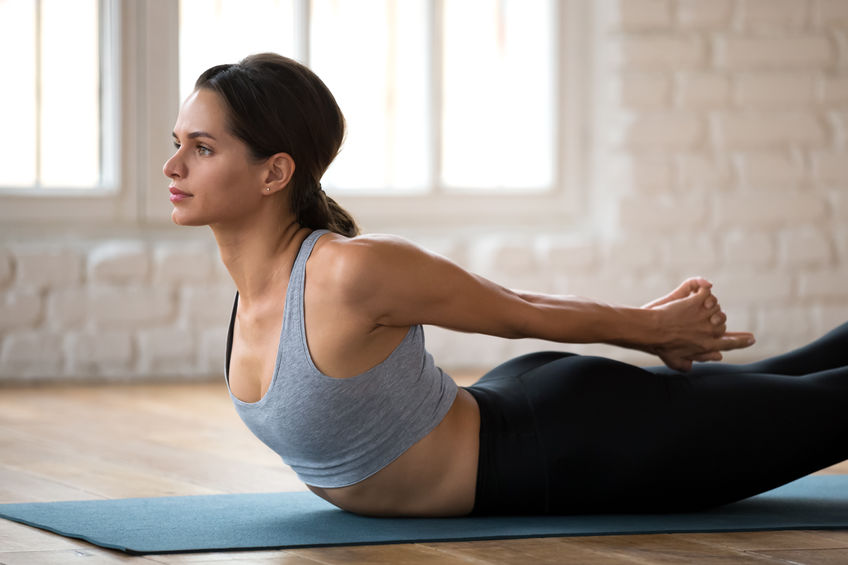 woman doing yoga locust pose